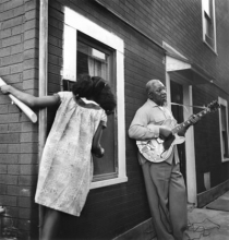 Joanne Leonard, Girl and Man with Guitar, West Oakland, mid 1960s. From the original negative in the collection of the Oakland Museum of California, gift of the artist.